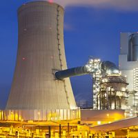 A modern brown coal power station with night blue evening sky. Panoramic wide angle shot.